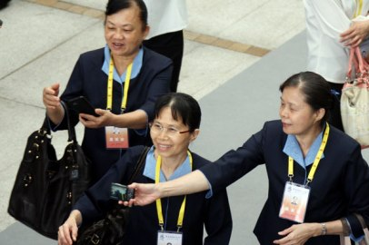 Taiwan delegation members take photos at the fifth Straits Forum in Xiamen, Fujian province, on Sunday. Photo by HU MEIDONG / China Daily
