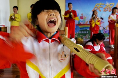 An Xingxing, 9, the youngest player in the team, practices percussion. It was the third bamboo tube that she has broken. Photo - Chinanews by Zhang Yuan