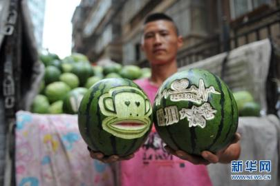 Shen Dongbin shows cartoon figures carved on watermelons at his watermelon stall in northwest China's Lanzhou on July 4, 2013. Photo Source Photo - Xinhua